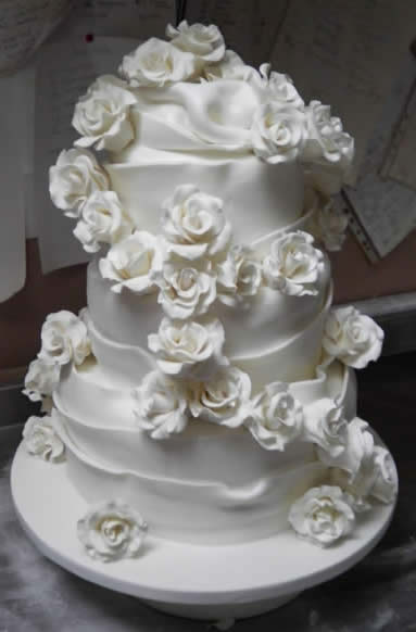 Beautiful white icing roses cascading down a stunningly iced wedding cake made by a Wedding Cake Professional in London